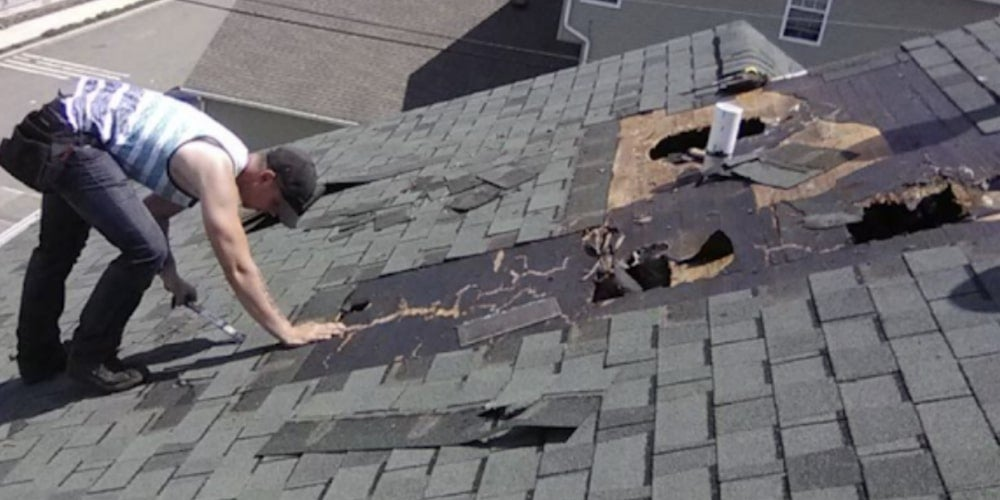 Contractor installing roof shingles