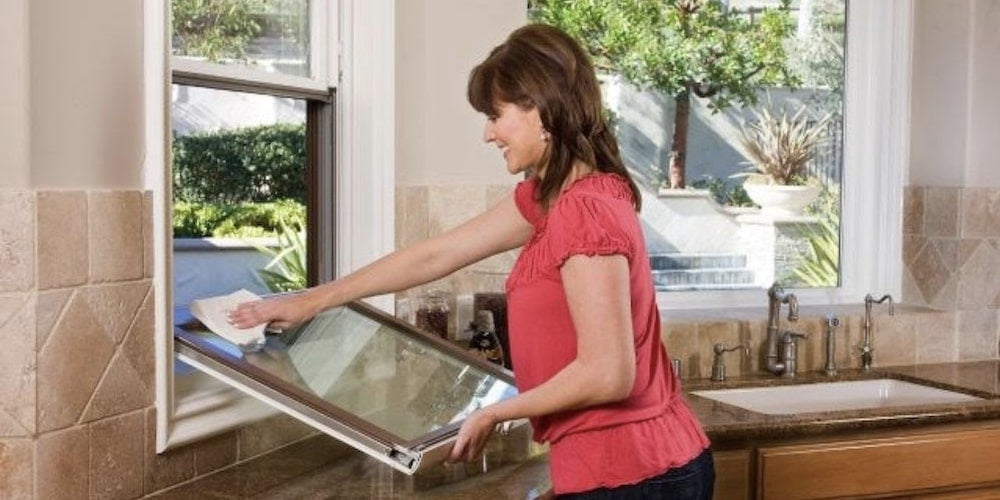 A woman cleaning her double-hung window in her kitchen