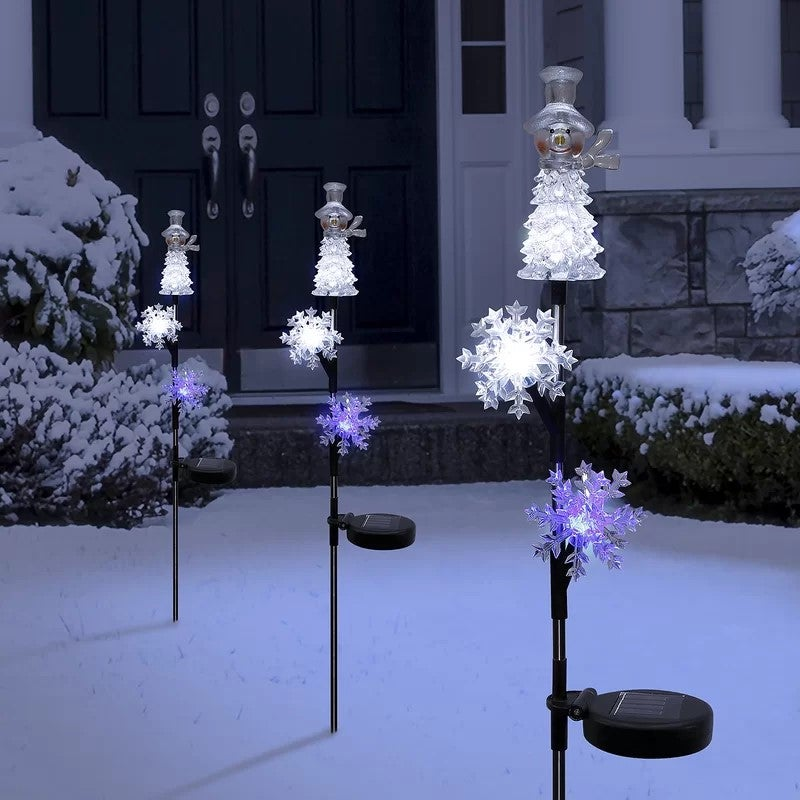 solar-powered snowmen yard stakes in the snow