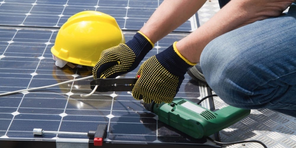 A professional installing solar panels on a roof