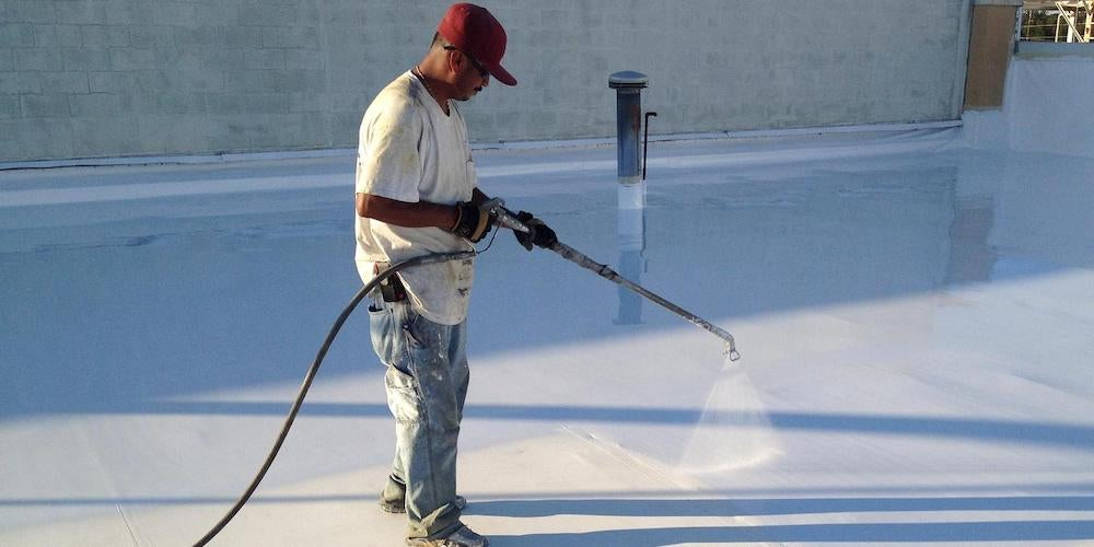 A contractor coating a flat roof