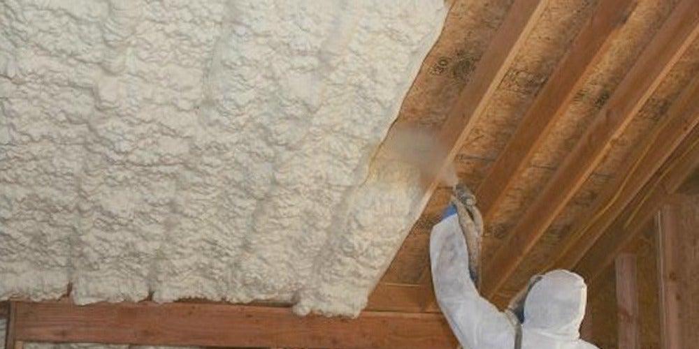Professional spraying foam insulation onto exposed attic walls