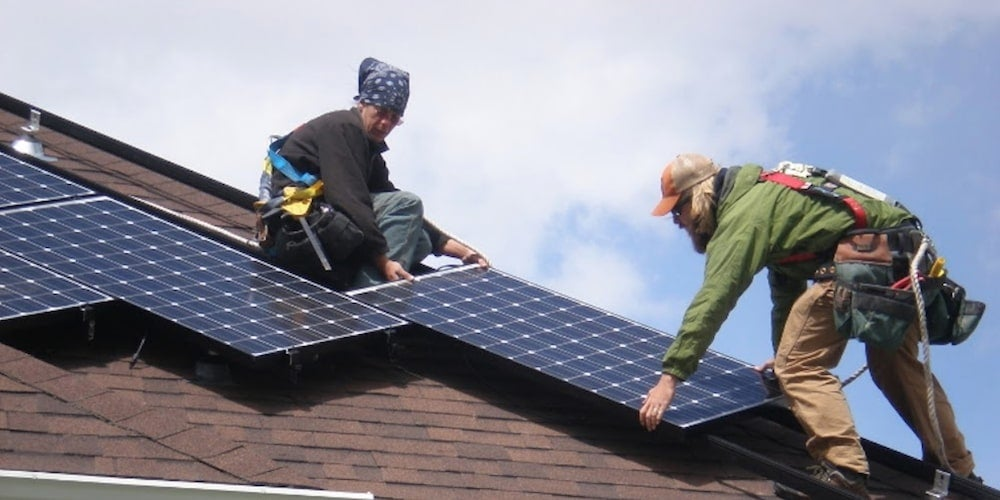 Two men installing standard rail system solar panels on a residential roof