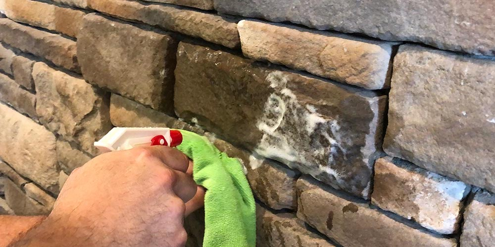 Homeowner maintaining stone siding by cleaning it withh soap and a rag