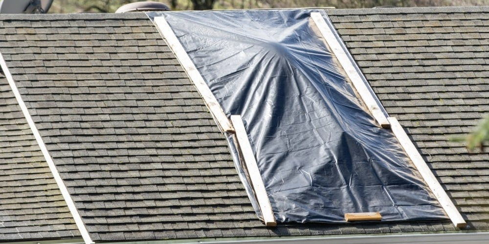 A tarp laying over a section of roof