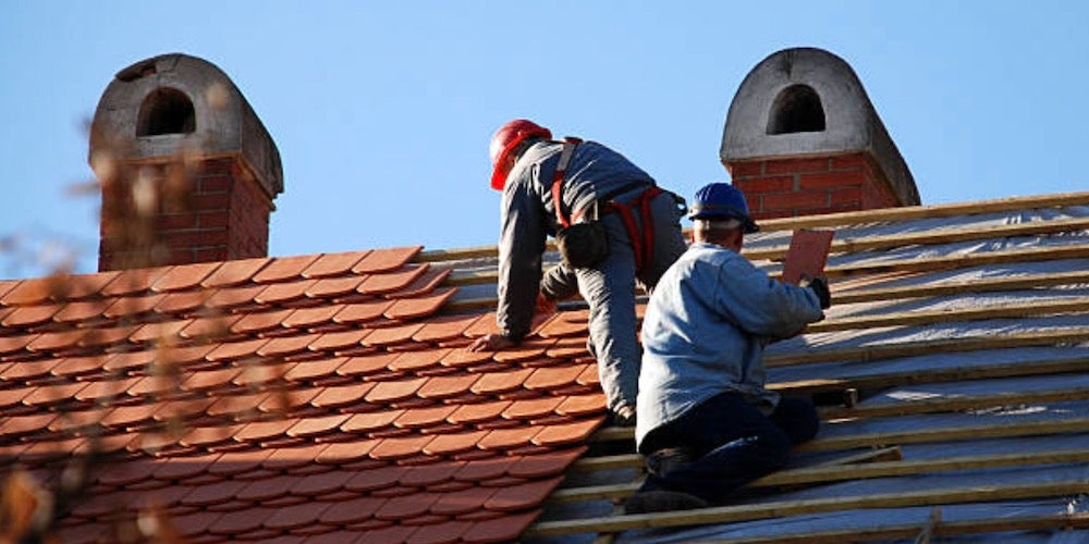 Two contractors installing clay tiles on a residential roof