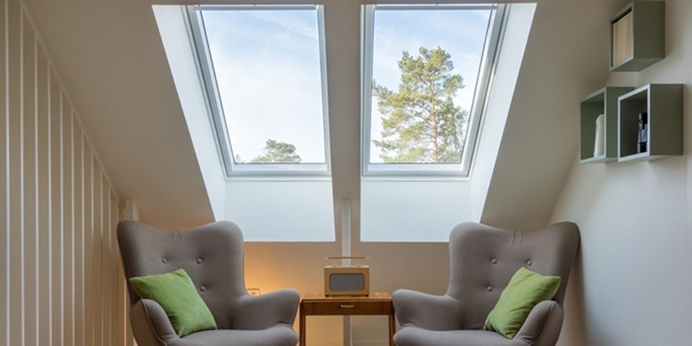 Skylights filtering natural light into a room with two gray chairs