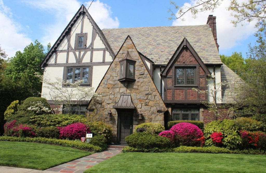 A tudor style home with brick and wooden enhancements