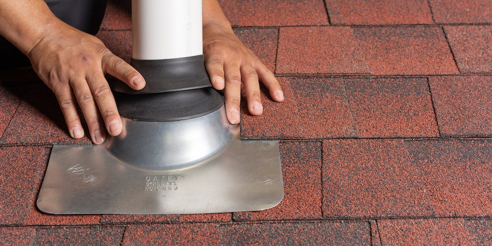 Vent pipe flashing being installed on a residential roof