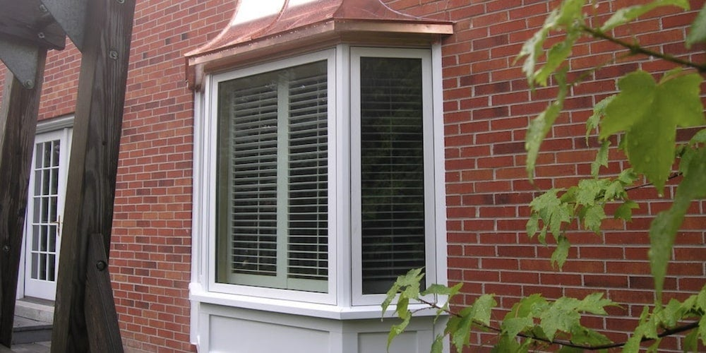 Vinyl bay window on a residential home with a copper roof