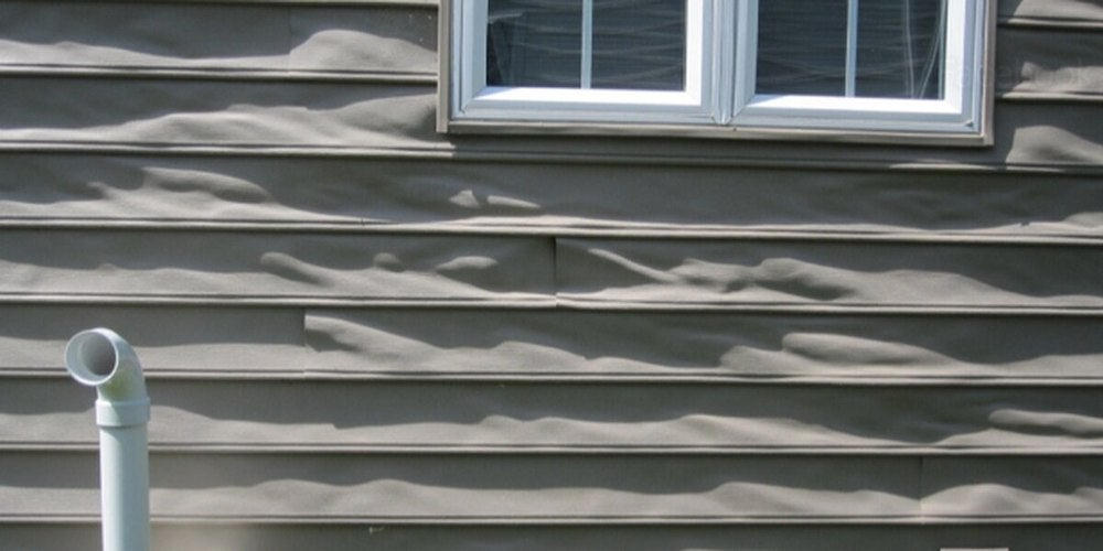 Warped vinyl siding on a residential home