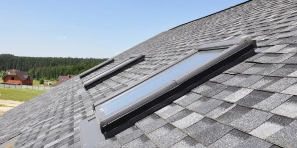 Three skylights installed in a row on a residential roof