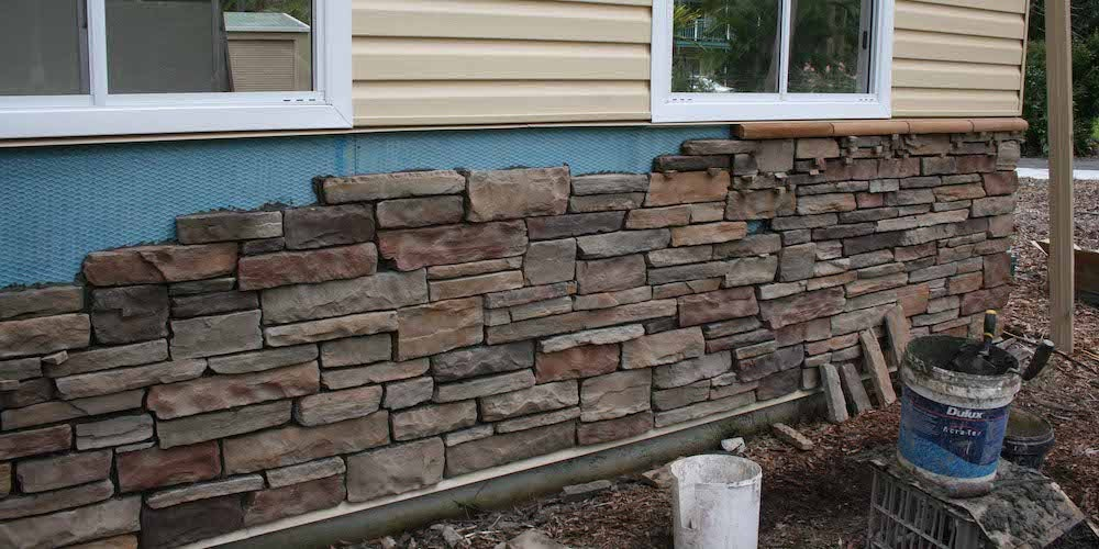 Stone veneer siding being installed on a residential home