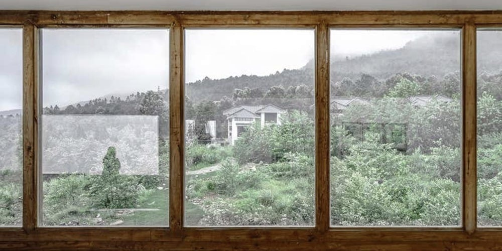 Wood picture window looking over a forest