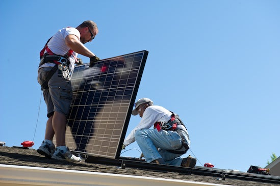 Installers put solar panels on a roof in Colorado. Courtesy NREL