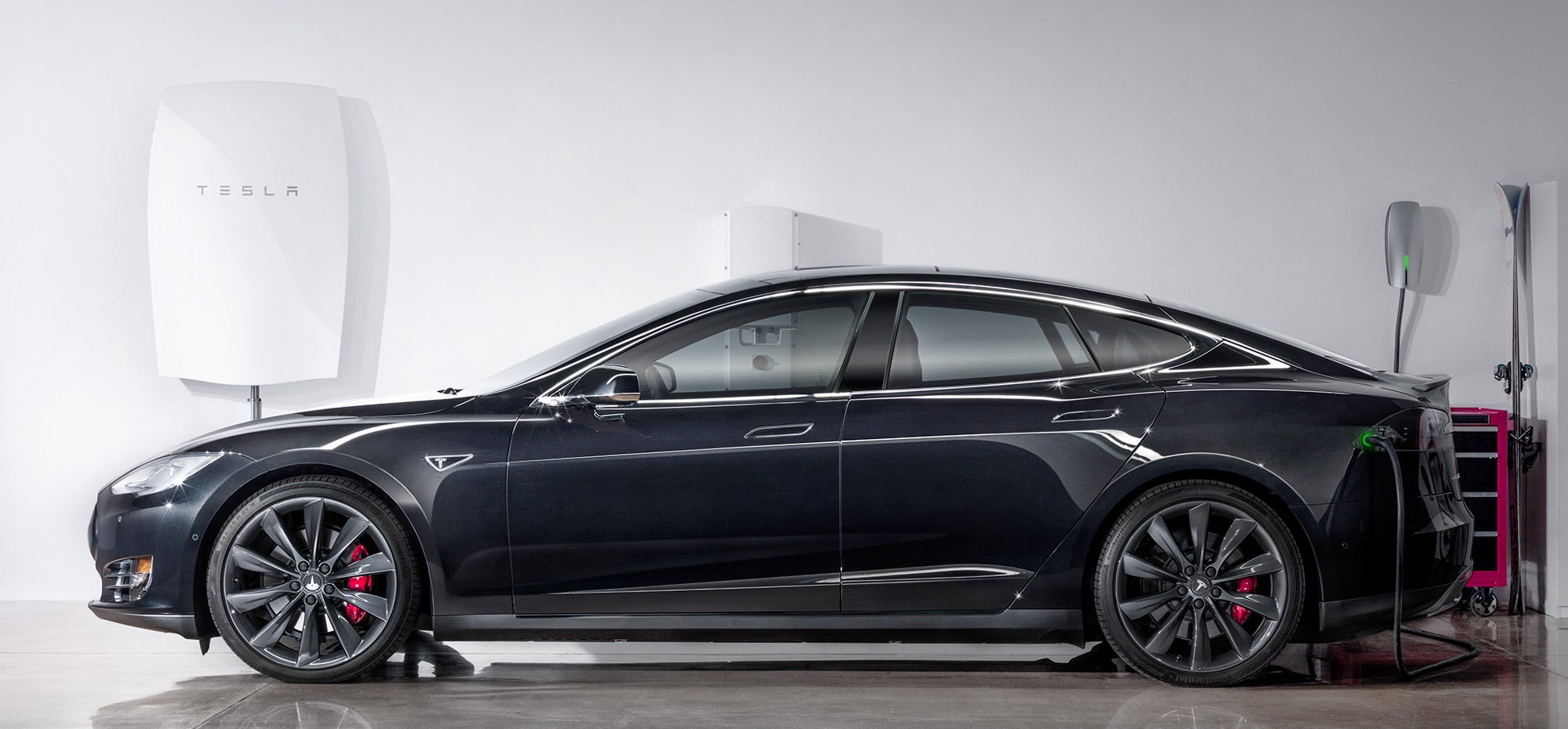 A Tesla Model S with the Powerwall in the background. Courtesy Tesla