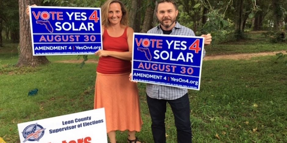 Solar supporters tout their signs. Courtesy Vote Solar