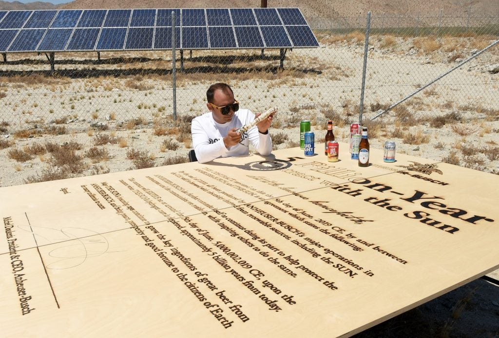 Solar artist Michael Papadakis signing contract. Courtesy AB-InBev